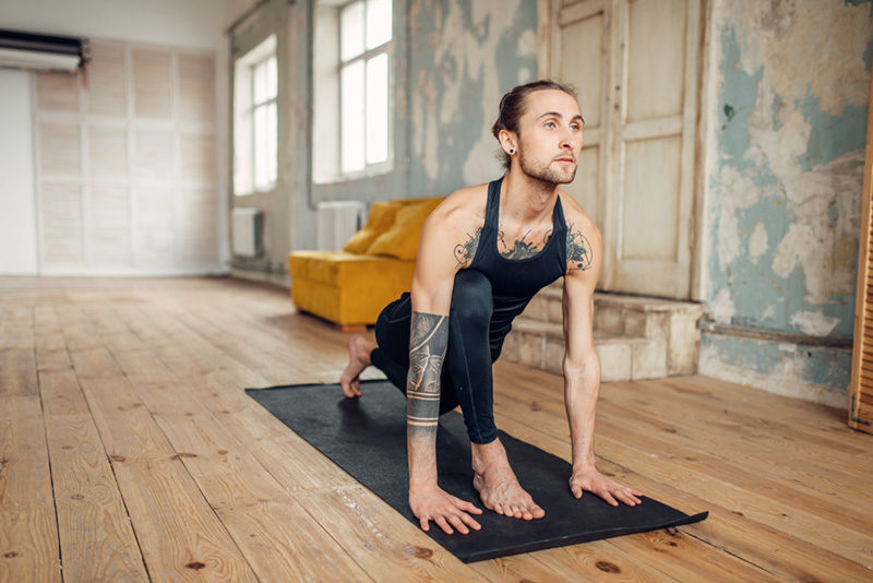 Tattooed person doing yoga