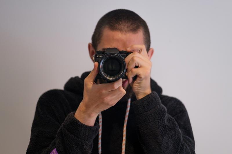 Man holding camera in landscape orientation